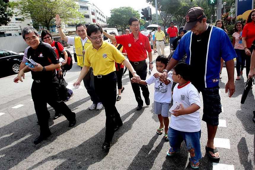 Minister for Education Heng Swee Keat with Aqil Nabic, 6; Mr Ang Hak Seng, chief executive director of the People's Association; Aniq Shabic, 7; Mr Jaidi, 39; and mother behind Ms Zaiton, 41. Mr Heng is promoting positive road safety behaviour in Tam