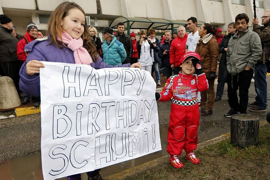 Kids celebrate with a placard the 45th birthday of seven-time Formula One world champion Michael Schumacher in front of the CHU hospital emergency unit in Grenoble, French Alps, where Schumacher is hospitalised, on Jan 3, 2014. -- PHOTO: REUTERS