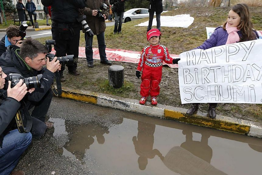 Kids pose for photographers as they celebrate with a placard the 45th birthday of seven-time Formula One world champion Michael Schumacher in front of the CHU hospital emergency unit in Grenoble, French Alps, where Schumacher is hospitalised, on Jan