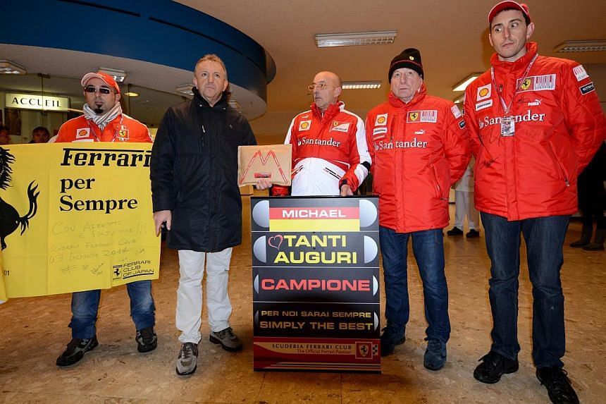 Fans of German Formula One world champion Michael Schumacher stand inside the Grenoble University Hospital Centre, to mark his 45th birthday, on Jan 3, 2014. -- PHOTO: AFP