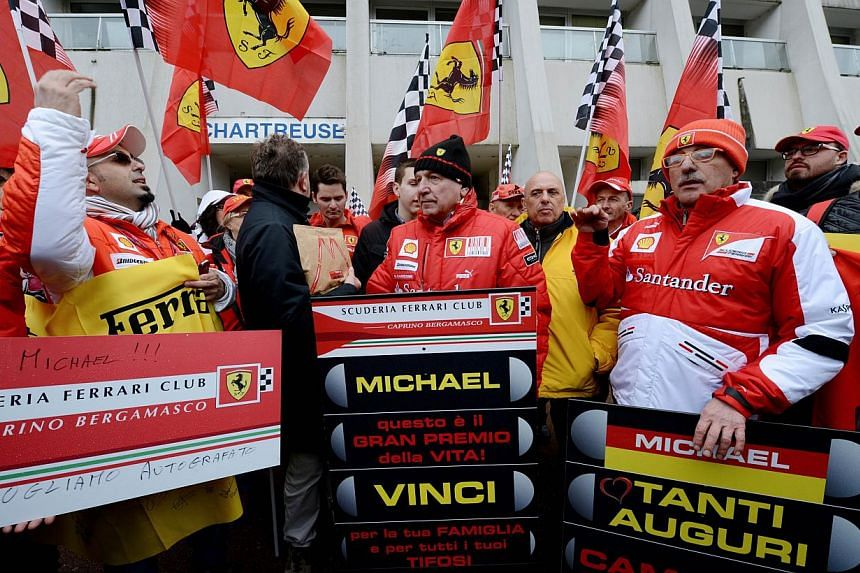 Fans of German Formula One world champion Michael Schumacher wear flags of the Ferrari Formula One team as they stand in front of the Grenoble University Hospital Centre, to mark his 45th birthday, on Jan 3, 2014. -- PHOTO: AFP