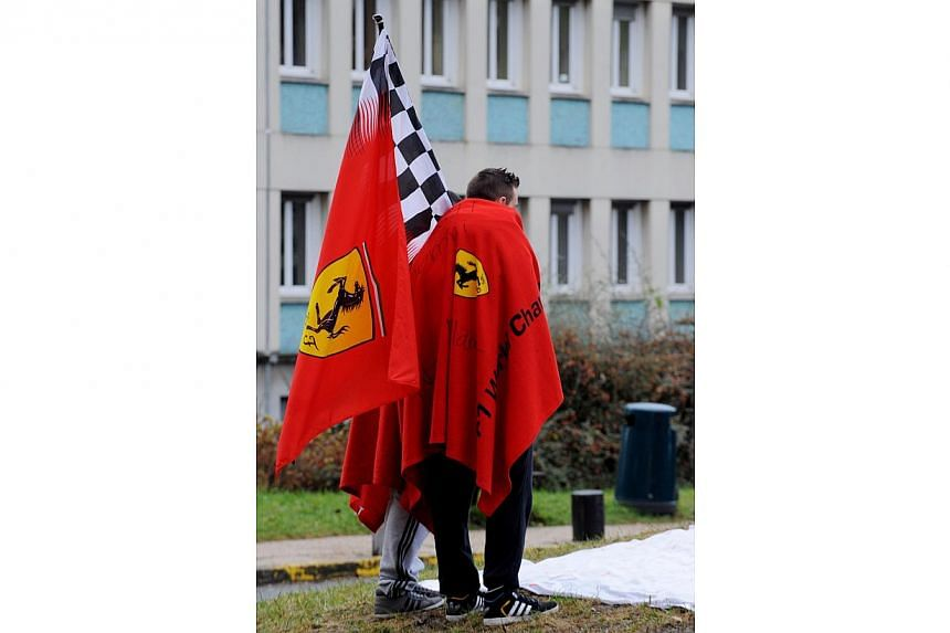 Fans of German Formula One world champion Michael Schumacher hold flags of the Ferrari Formula One team as they stand in front of the Grenoble University Hospital Centre, to mark his 45th birthday, on Jan 3, 2014. -- PHOTO: AFP