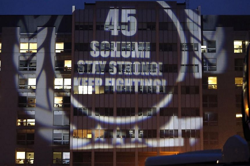 A message to mark the 45th birthday of seven-time Formula One world champion Michael Schumacher is projected by fans on the facade of the CHU hospital emergency unit in Grenoble, French Alps, where Schumacher is hospitalized on Jan 3, 2014.Ferr