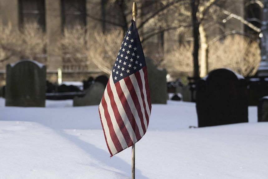Snow lies around the United States national flag at Trinity Church Cemetery during a winter storm in New York on Jan 3, 2014. -- PHOTO: REUTERS