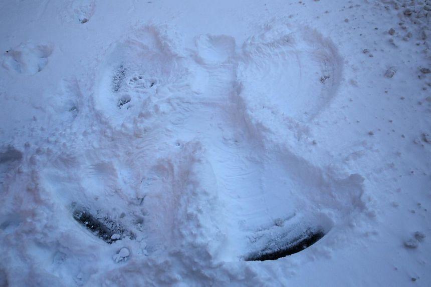 """A """"snow angel"""" lies along a Manhattan street in New York following Winter Storm Hercules on Jan 3, 2014. -- PHOTO: AFP"""