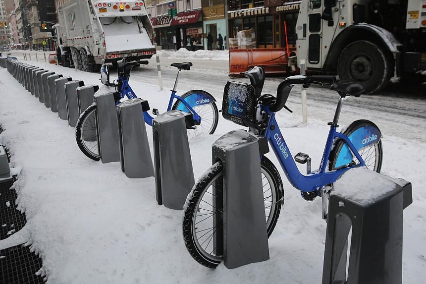 Garbage trucks plow past a Citi Bike station in New York after Winter Storm Hercules on Jan 3, 2014. -- PHOTO: AFP