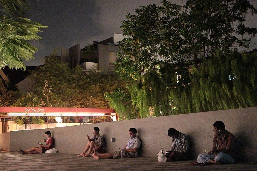 People making use of the free Wi-Fi access outside myVillage mall in Serangoon Gardens. Scouting for free Wi-Fi zones is a popular pursuit among foreign workers who are becoming increasingly Web- and social media-savvy. -- ST PHOTO: NEO XIAOBIN