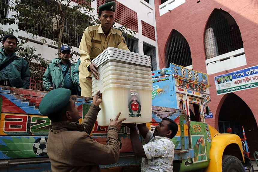 Security personnel unload ballot boxes from a truck at a polling centre ahead of parliamentary elections in Dhaka on Jan 4, 2014. Bangladesh voted on Sunday in a violence-plagued election that will end in certain victory for Prime Minister Sheikh Has