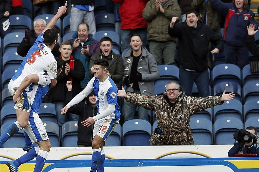 Blackburn Rovers' Grant Hanley (left) jumps on a teammate's back as they celebrate Scott Dann's goal during their FA Cup third round soccer match against Manchester City at Ewood Park in Blackburn, northwest England on Jan 4, 2014. Last season's beat