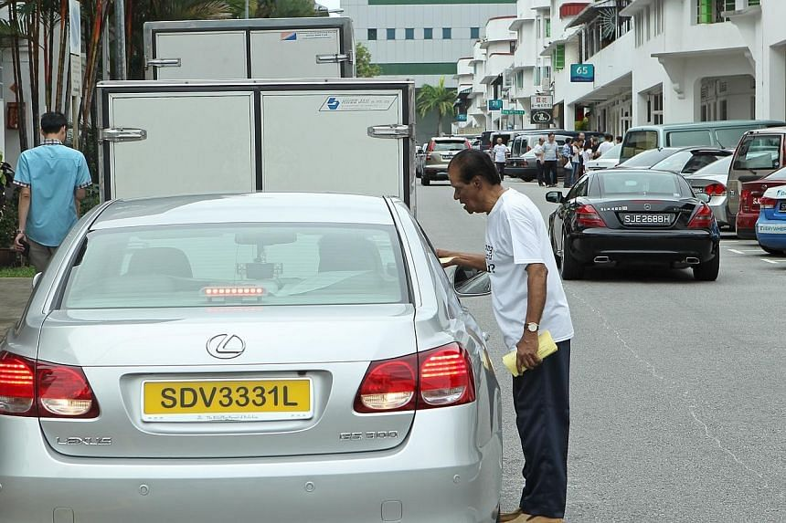 Mr Radha, a resident at the old Tiong Bahru estate for the past 50 years, gives out leaflets encouraging drivers to park in designated lots and encourage civic-minded behaviour among visitors of the estate.-- ST PHOTO:SEAH KWANG PENG