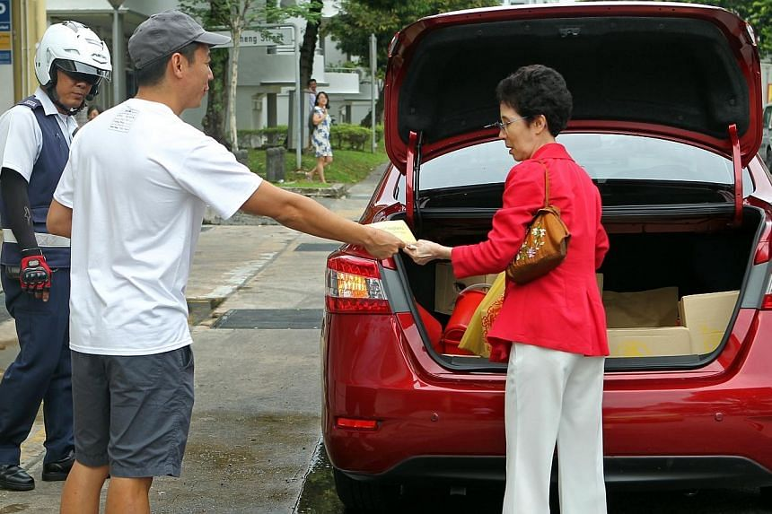 A Land Transport Authority enforcement officer looks on as Tiong Bahru resident Choa Haw King (centre) gives out leaflets encouraging drivers to park in designated lots and encourage civic-minded behaviour among visitors of the estate.-- ST PHO
