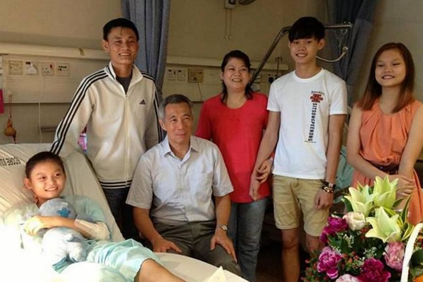 Injured 14-year-old Tan Li Xuan, who had her right hand crushed in a sugarcane juicer accident two weeks ago, received a visit from a special guest - Prime Minister Lee Hsien Loong (third from left). -- PHOTO: FACEBOOK PAGE OF PM LEE HSIEN LOONG