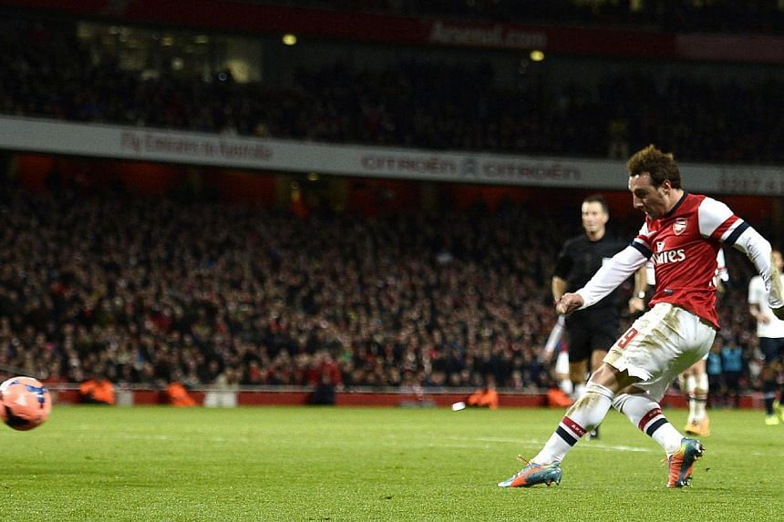 Arsenal's Santi Cazorla (right) scores a goal against Tottenham Hotspur during their English FA Cup soccer match at the Emirates stadium in London, on Jan 4, 2014. Arsenal reached the fourth round of the FA Cup when they beat arch-rivals Tottenham Ho