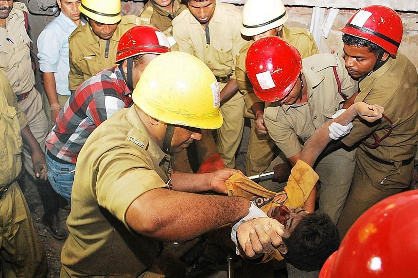 Rescue workers pull an injured victim from the rubble of a collapsed building under construction in Canacona, about 80km from the capital Panaji of western Goa state on Saturday, Jan 4, 2014. Indian rescuers were racing on Sunday to try to save