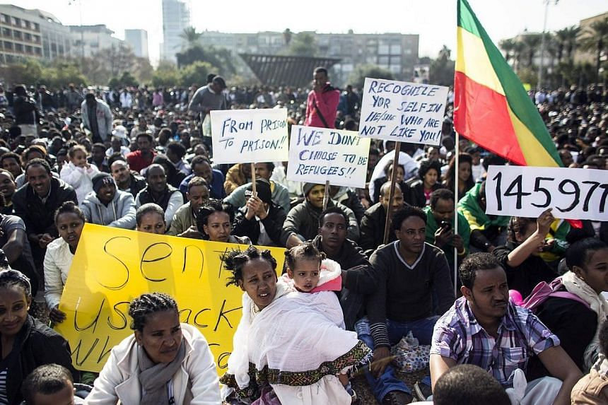 African migrants hold signs during a protest at Rabin Square in Tel Aviv, on Jan 5, 2014.-- PHOTO: REUTERS