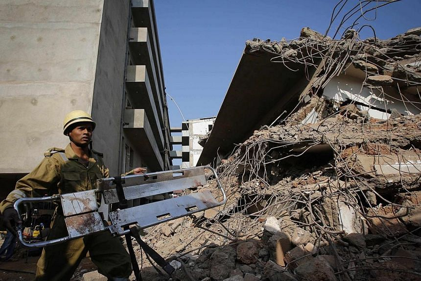 A rescue worker carries a stretcher at the site of a collapsed building that was under construction in Canacona town in the western Indian city of Goa, on Sunday, Jan 5, 2014. -- PHOTO: REUTERS