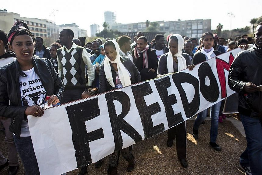 African migrants hold a sign during a protest at Rabin Square in Tel Aviv, on Jan 5, 2014.-- PHOTO: REUTERS