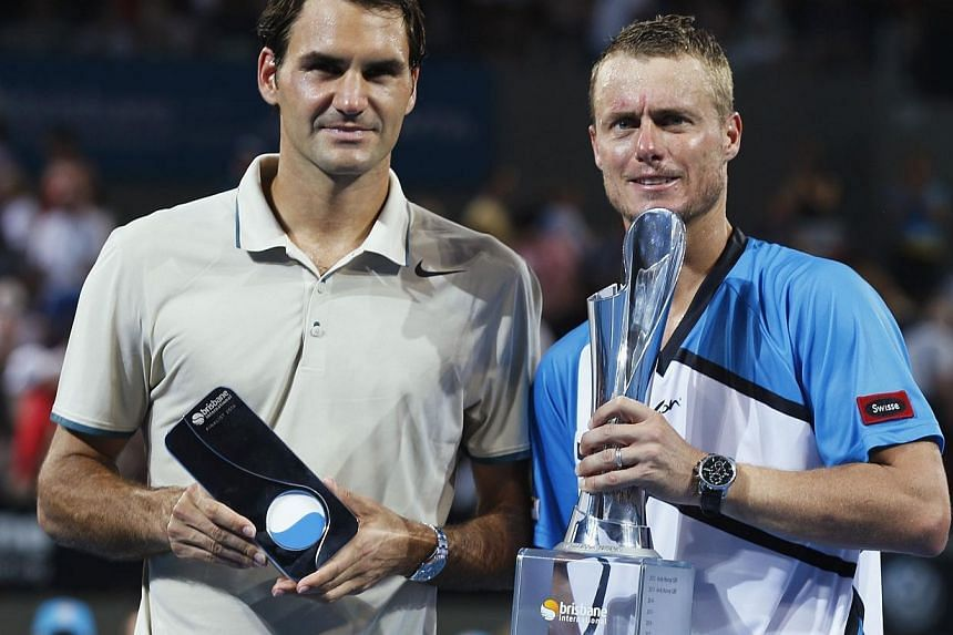 Lleyton Hewitt of Australia(right)poses with Roger Federer of Switzerlandafter the trophy presentation for the men's singles final match at the Brisbane International tennis tournament in Brisbane, January 5, 2014.Hewitt delig