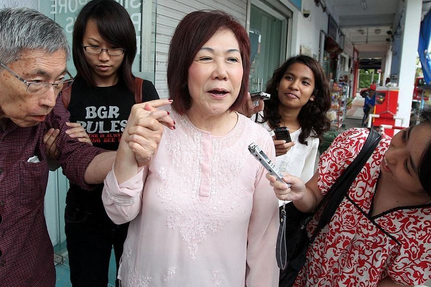 Singapore People's Party (SPP) chairman Lina Chiam (centre) speaks to reporters as she guides her husband, Chiam See Tong (far left), out of the SPP headquarters after an election meeting on Sunday, Jan 5, 2013. -- ST PHOTO: JASON