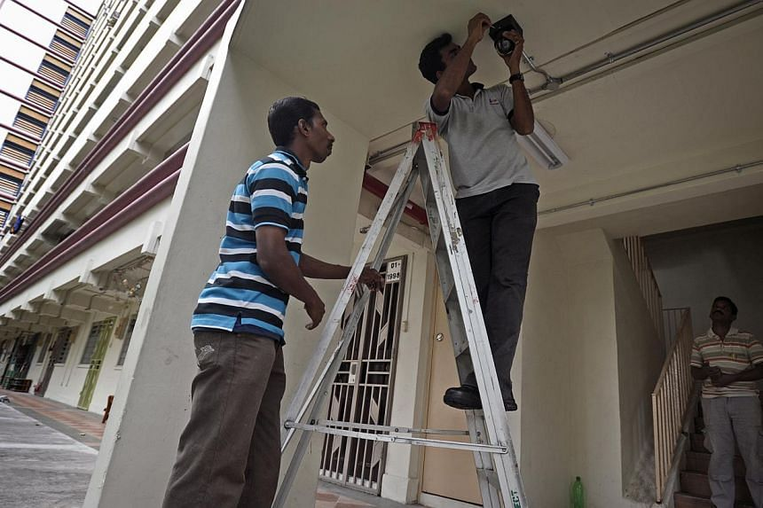 A CCTV camera being installed at the foot of a stairwell at an HDB block in Jalan Bukit Merah. With more electronic eyes watching over the heartland, loan shark harassment cases are set to reach a new low since 2010. -- ST PHOTO: JOSEPH NAIR