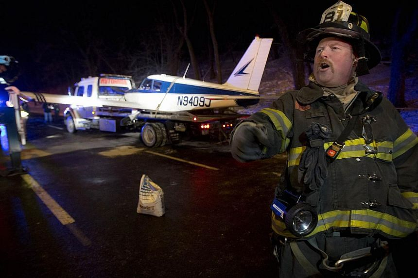 A single engine plane is loaded onto a flat bed truck after landing on Major Deegan Expressway in the Bronx borough of New York on Jan 4, 2014. A small plane made an emergency landing on a highway in the Bronx borough of New York, injuring the pilot