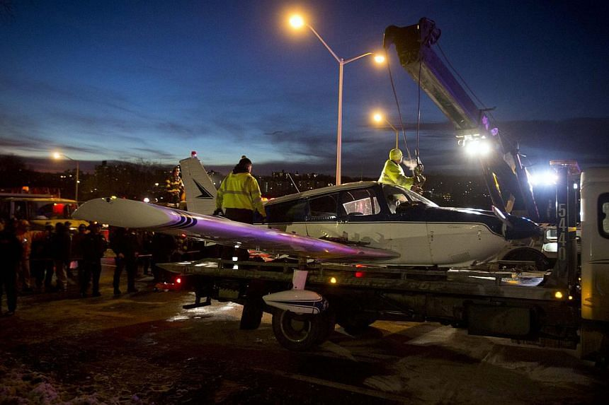 A single engine plane is lifted onto a flat bed truck after landing on Major Deegan Expressway in the Bronx borough of New York on Jan 4, 2014. -- PHOTO: REUTERS