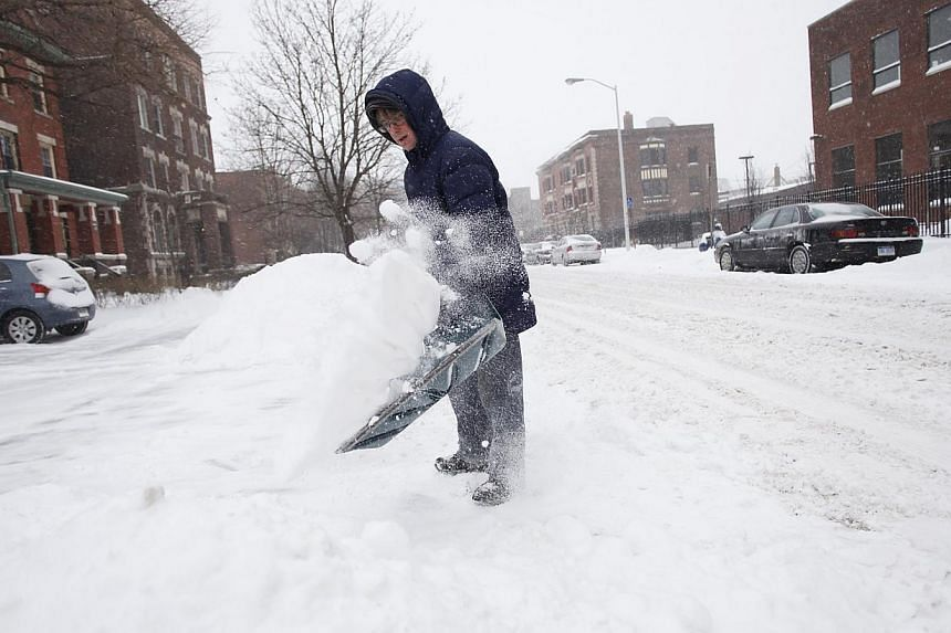 Mr Greg Mauch uses a shovel to clear several inches of snow from her sidewalk in Detroit, Michigan on Jan 2, 2014. Many parts of the United States (US) Midwest braced for a blast of Arctic air this weekend that could bring some of the coldest tempera