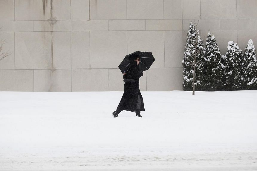 A woman uses a umbrella to protect her from the snow in Detroit, Michigan on Jan 2, 2014. Many parts of the United States (US) Midwest braced for a blast of Arctic air this weekend that could bring some of the coldest temperatures in two decades befo