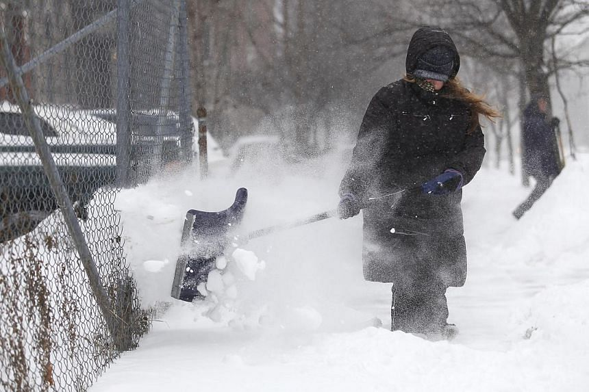 Ms Heather Miller uses a shovel to clear several inches of snow from her sidewalk in Detroit, Michigan on Jan 2, 2014. Many parts of the United States (US) Midwest braced for a blast of Arctic air this weekend that could bring some of the coldest tem