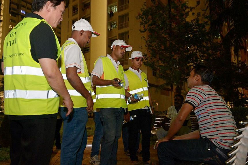 (From left) Grassroots leader Sunnie Tan and foreign workers Rajagopal Shanmugam, 34, Mohammad Aslam, 40, and Piyash Banik, 24, speaking to workers sitting in open areas at Teban Gardens. The foreign worker ambassadors join police and grassroots volu