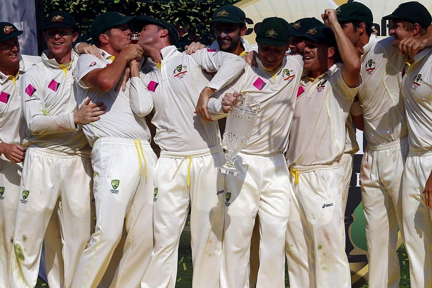 """Australia's captain Michael Clarke (4th L) and Peter Siddle (3rd L) kiss the""""Replica Ashes Urn"""" as they celebrate with their teammates after winning the fifth Ashes cricket test against England at the Sydney Cricket Ground on Jan 5, 2014. Australia's"""
