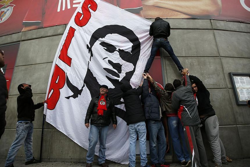 Supporters of Benfica hang a flag depicting a portrait of Eusebio at Luz stadium in Lisbon on Jan 5, 2014. -- PHOTO: REUTERS