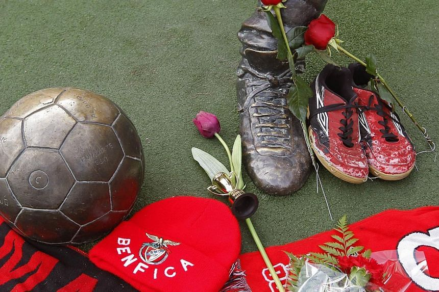 A picture taken on Jan 5, 2014 shows tributes left by fans near a statue of late Portuguese football player Eusebio da Silva Ferreira, also known as the 'Black Panther', outside the Luz stadium in Lisbon. -- PHOTO: AFP