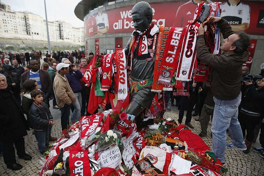 A man puts a Benfica scarf on the Eusebio monument at Luz stadium in Lisbon on Jan 5, 2014. The bronze statue of Benfica legend Eusebio in front of Lisbon's Stadium of Light was covered with flowers, scarves and messages as Portugal mourned the iconi