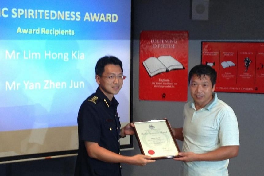 Mr Yan Zhen Jun, 44, who was the driver of the tipper truck, receiving the SCDF Public Spiritedness Award from Col Ling Young Ern, Commander 4th Civil Defence Division. Two members of the public were on Monday recognised by the Singapore Civil Defenc