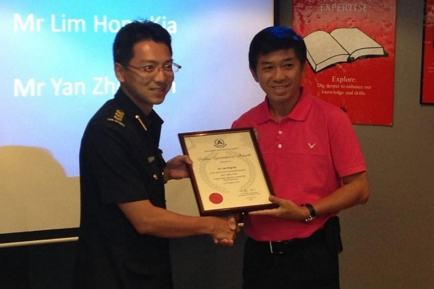 Mr Lim Hong Kia, 53, who isself-employed, receiving the SCDF Public Spiritedness Award from Col Ling Young Ern, Commander 4th Civil Defence Division. -- ST PHOTO: WALTER SIM