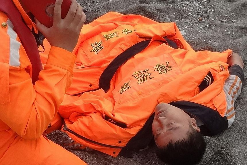 This handout photo taken on Jan 5, 2014, and received from the Taiwanese Coast Guard on Jan 6 shows Tseng Lien-fa (centre) receiving treatment from coast guards and fire station members in Taitung county, south-east Taiwan. -- PHOTO: AFP/TAIWAN COAST