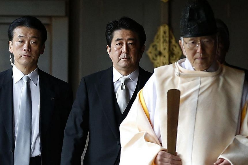 Japan's Prime Minister Shinzo Abe (centre) is led by a Shinto priest as he visits Yasukuni shrine in Tokyo, on Dec 26, 2013. Prime Minister Abe said on Monday he wanted to meet Chinese and South Korean leaders to explain why he visited a controv