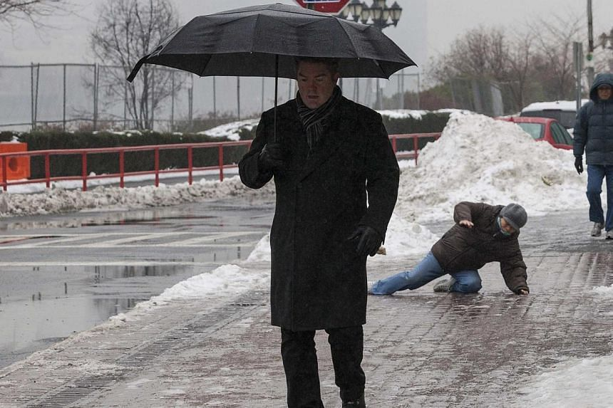 A man falls while slipping on ice during freezing rain on Roosevelt Island, a borough of Manhattan in New York Jan 5, 2014. Millions of people across the United States on Monday made last minute preparations for an unusually bitter Arctic blast that