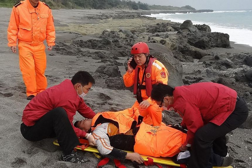 This handout photo taken on Jan 5, 2014, and received from the Taiwanese Coast Guard on Jan 6 shows Tseng Lien-fa (centre) receiving treatment from coast guards and fire station members in Taitung county, south-east Taiwan. Mr Tseng miraculously surv
