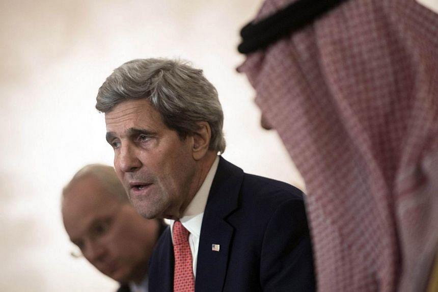 Saudi Arabia's Minister of Foreign Affairs Prince Saud Al-Faisal bin Abdulaziz al-Saud (right) listens as U.S. Secretary of State John Kerry makes a statement to the press at King Khalid International Airport in Riyadh on Jan 5, 2014. US Secretary of