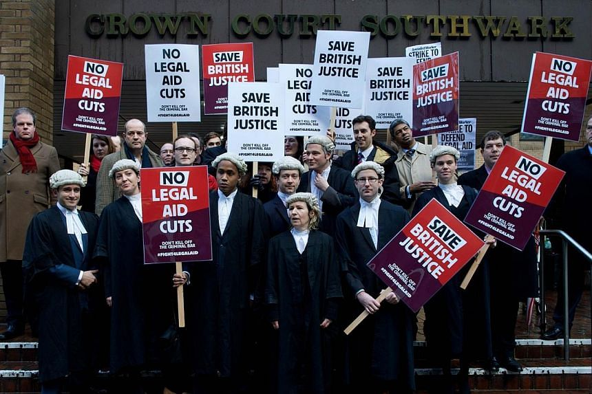 British legal professionals hold placards during a protest against cuts to the legal aid budget during a protest outside Southwark Crown Court in London, on Jan 6, 2014.British criminal case lawyers staged an unprecedented walkout on Monday, Ja