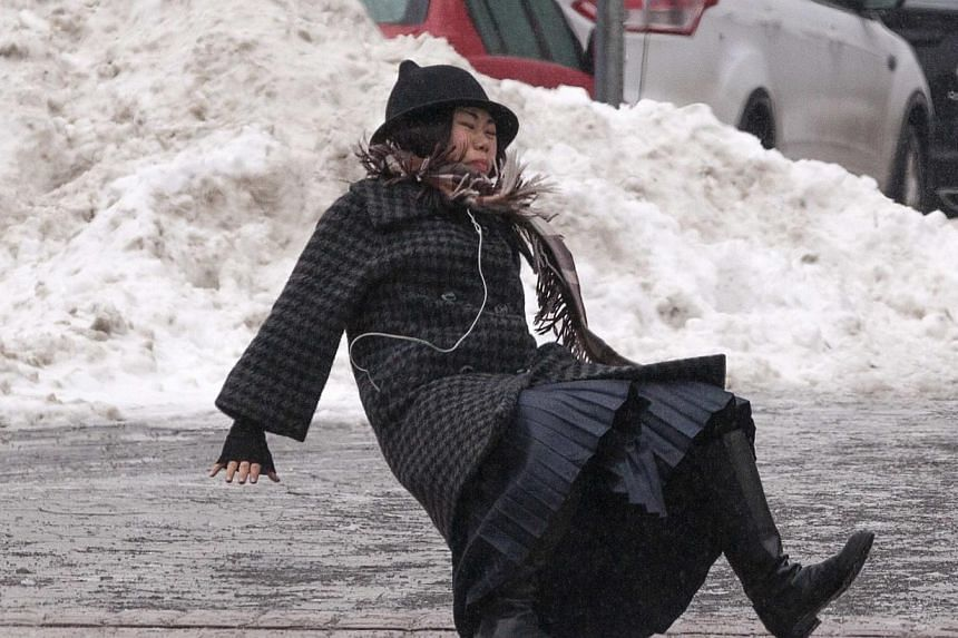 A woman falls while slipping on ice during freezing rain on Roosevelt Island, a borough of Manhattan, in New York, on Jan 5, 2014. -- PHOTO: REUTERS