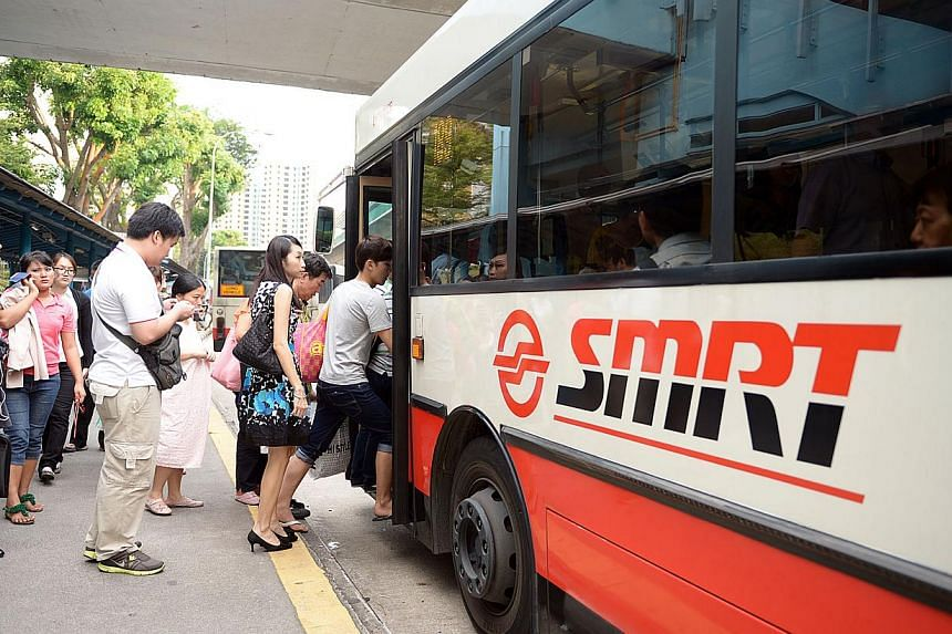 Commuters boarding a SMRT bus near Clementi MRT station. A system that penalises and rewards bus operators for service reliability will begin with 15 services in the first quarter. -- ST FILE PHOTO: DESMOND WEE