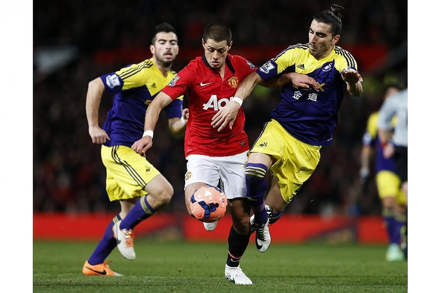 Manchester United's Javier Hernandez (centre) is tackled by Swansea City's Chico Flores (right) during their English FA Cup third round soccer match at Old Trafford on Jan 5, 2014. Manchester United suffered a stinging 2-1 home defeat by Swansea City