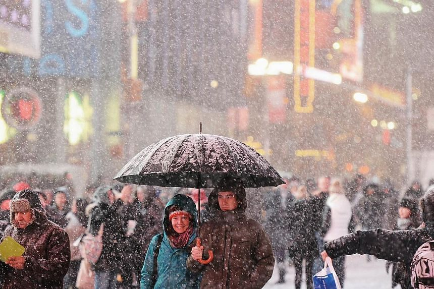Visitors enjoy the snow on Broadway January 2, 2014 on Times Square in New York. Forecasters are predicting up to seven inches of snow in New York. Snowfall in the northeastern United States caused flight cancellations and airport delays while federa