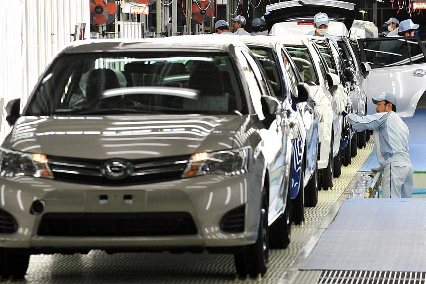"In a file picture taken on May 11, 2012 workers check paints and bodies of the new model of Toyota Motor's best selling car ""Corolla"" at a plant of the company's subsidiary Central Motor at Ohira village in Miyagi prefecture, northern Japan. Toyota M"