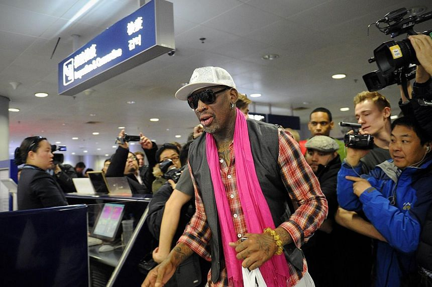 Former NBA basketball player Dennis Rodman of the US (centre) walking past the media to check in for his flight to North Korea at Beijing's international airport on Jan 6, 2014. Rodman arrived in North Korea on Jan 6, 2014, with a team of retired pro
