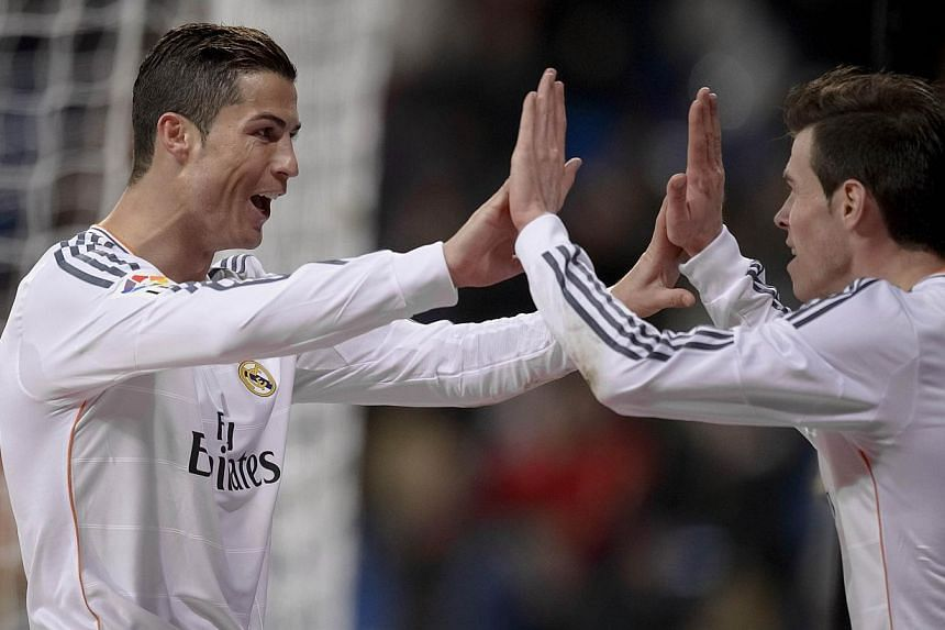 Real Madrid's Portuguese forward Cristiano Ronaldo celebrates with Real Madrid's Welsh striker Gareth Bale after scoring his second goal during the Spanish league football match between Real Madrid and RC Celta de Vigo at the Santiago Bernabeu stadiu