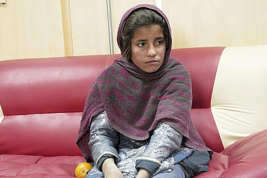 Sphozmay, 10, who was about to be used by the Taliban as a suicide bomber, sits at a police office in Helmand province in this police handout photo released on Jan 6, 2014. -- PHOTO: REUTERS